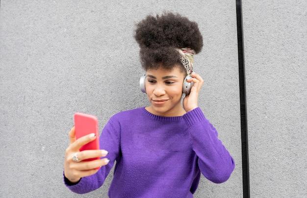 ヘッドフォンとsmarpthoneを歩いている通りで若いきれいな女性