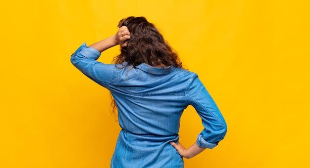 노란색 배경에 젊은 예쁜 여자. 뒷면보기
