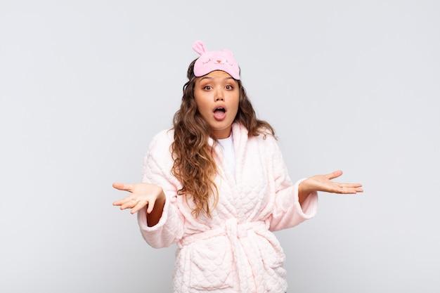 口を開けて驚いた若いきれいな女性は、パジャマを着て信じられないほどの驚きにショックを受けて驚いた