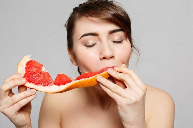 若いきれいな女性または長い髪のかわいいセクシーな女の子は、グレープフルーツのフルーツスライスを保持し、