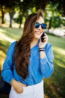 휴대 전화에 대 한 얘기는 공원에서 야외에서 젊은 예쁜 여자