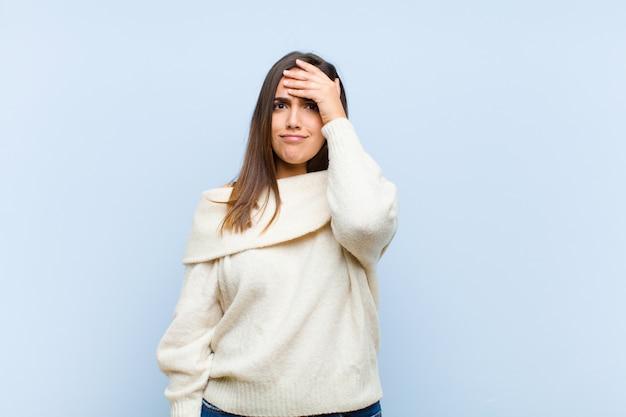Молодая красивая женщина паникует за забытый крайний срок, чувствуя стресс, приходится скрывать беспорядок или ошибку на синем фоне