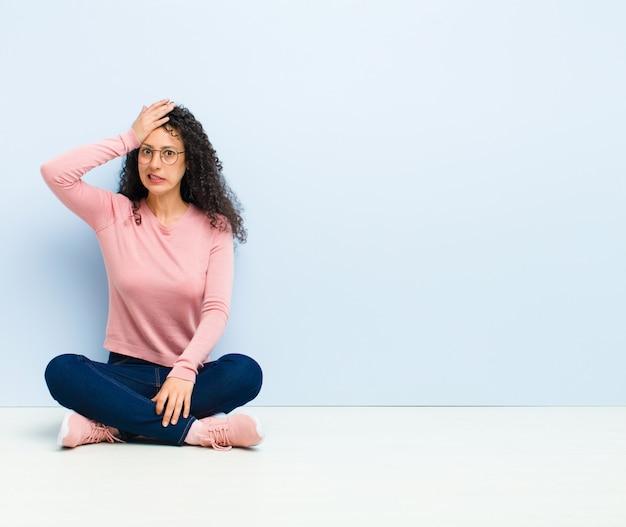 Молодая симпатичная женщина паникует за забытый крайний срок, чувствуя стресс, ей приходится скрывать беспорядок или ошибку, сидя на полу