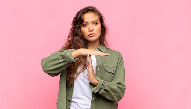 Young pretty woman on pink background. time-out gesture