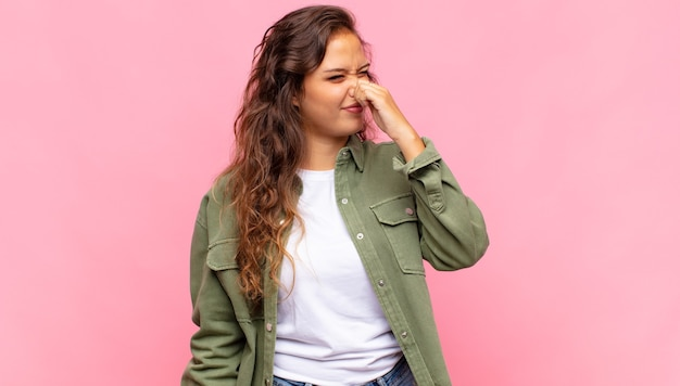 Young pretty woman on pink background