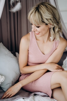 A young pretty woman in a pink dress having a rest on the bed