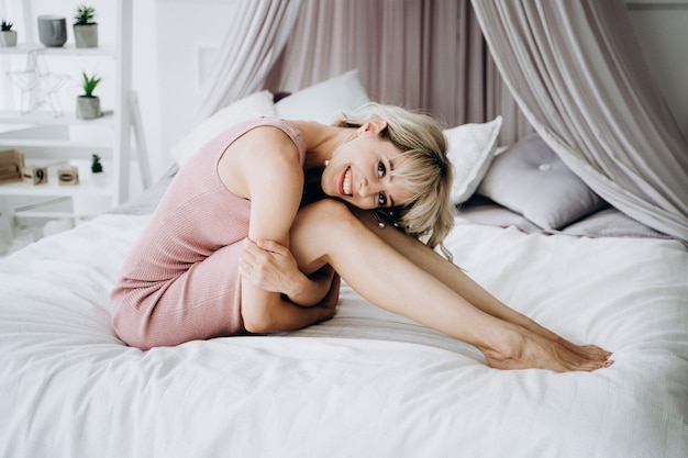 A young pretty woman in a pink dress having a rest lying on the bed