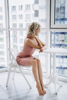 A young pretty woman in a pink dress sitting near the window
