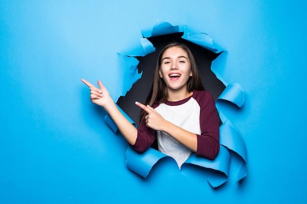 젊은 예쁜 여자는 종이 벽에 파란색 구멍을 통해 보면서 측면을 지적했다.