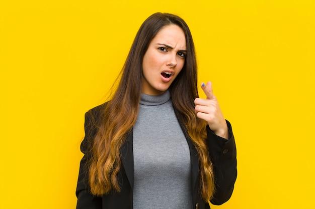 Молодая красивая женщина, указывая на камеру с злой агрессивным выражением лица, как бешеный, сумасшедший босс