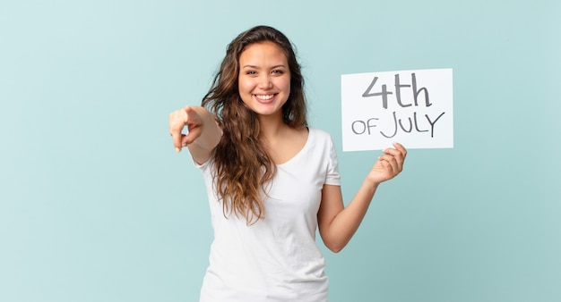 7月4日のテキストで正面を指している若いきれいな女性