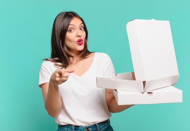 테이크 아웃 피자를 가리키거나 보여주고 들고 있는 젊은 예쁜 여자와 테이크 아웃 피자를 들고