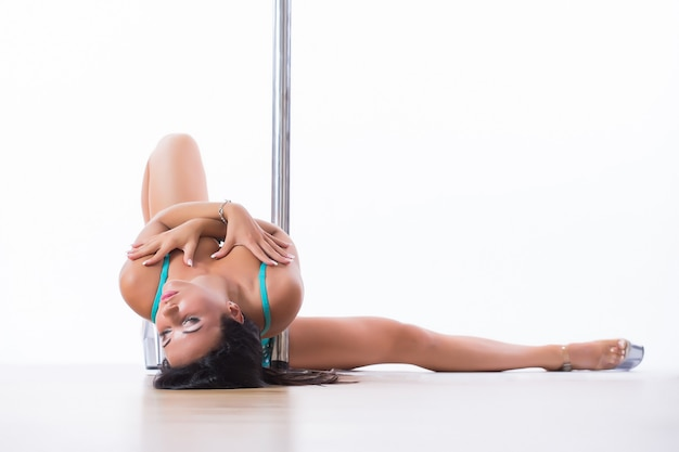 Young pretty woman pole dancer isolated on white background