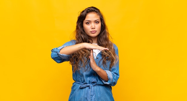 Young pretty woman posing against the colored wall
