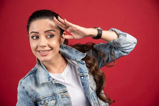 Giovane donna graziosa che posa in giacca di jeans su uno sfondo rosso. foto di alta qualità