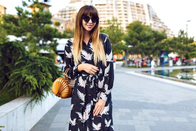 우아한 긴 드레스와 빈티지 밀짚 유행 가방을 입고 도심에서 거리에서 포즈를 취하는 젊은 예쁜 여자, 분위기를 즐기십시오,