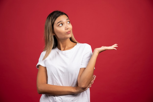 Giovane donna graziosa che posa sulla parete rossa.