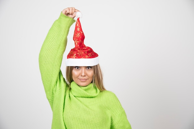 Giovane donna graziosa che posa in cappello rosso di babbo natale.