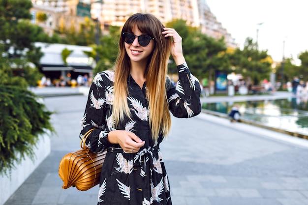 Giovane bella donna in posa sulla strada al centro della città, indossando un elegante abito lungo e una borsa alla moda di paglia vintage, goditi l'atmosfera,