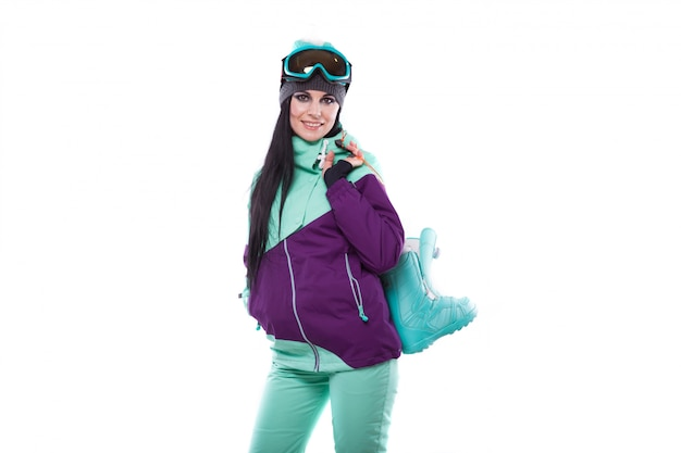 Young pretty woman in purple ski costume and ski glasses hold blue snow boots
