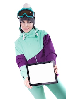 Young pretty woman in purple ski costume and ski glasses hold empty tablet