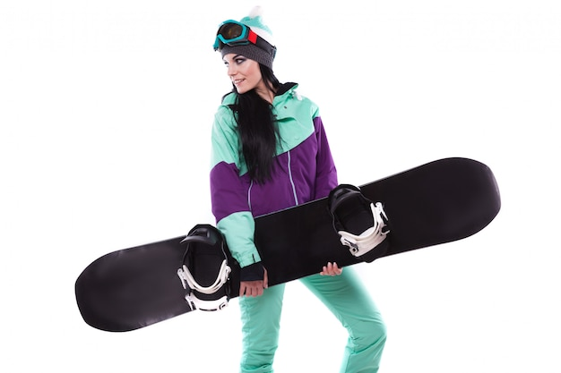 Young pretty woman in purple ski suit hold snowboard
