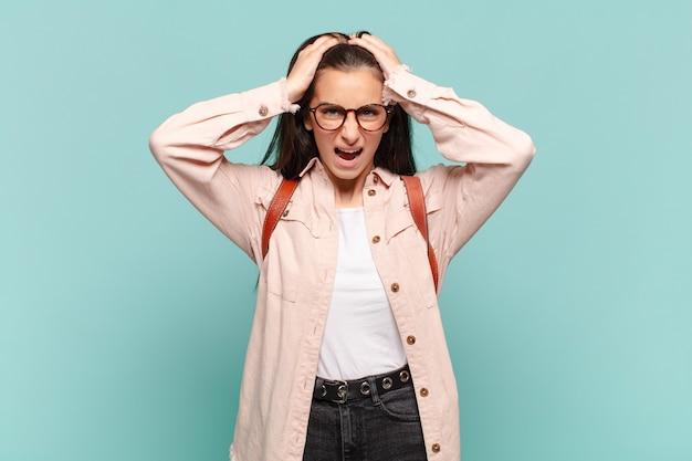 Молодая симпатичная женщина поднимает руки к голове, с открытым ртом, чувствуя себя чрезвычайно удачливой, удивленной, взволнованной и счастливой. студенческая концепция