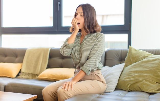 Молодая красивая женщина отдыхает дома на диване