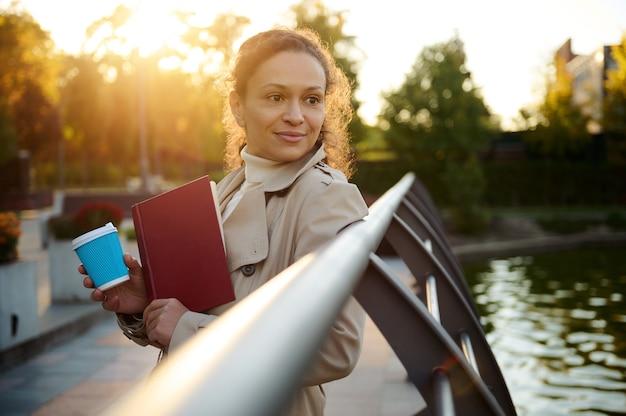 젊고 예쁜 여성은 테이크아웃 종이 머그컵과 손 책을 들고 가을 도시 공원에서 노란색 황금빛 잎사귀 배경에 떨어지는 햇빛과 함께 카메라를 바라보며 웃고 있습니다. 가을