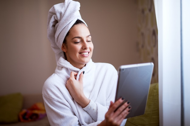 Young pretty woman in robe is smiling and feeling fresh after the shower while using tablet near a window.