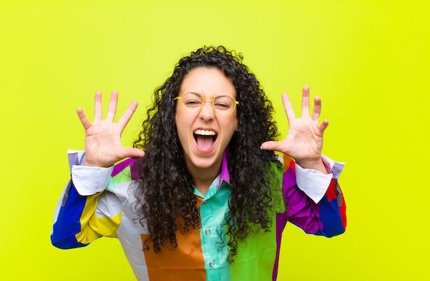 クロマキーの壁に頭の横にある手でパニックや怒り、ショック、恐怖、激怒で叫んでいる若いきれいな女性