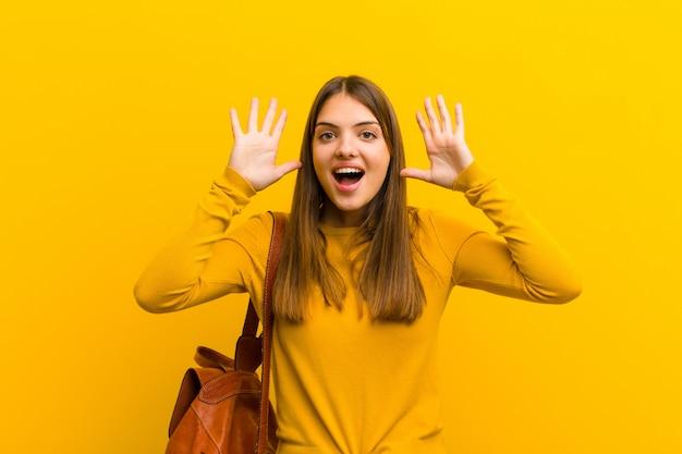 オレンジ色の壁に頭の横に手でパニックや怒り、ショック、恐怖、激怒で叫んでいる若いきれいな女性
