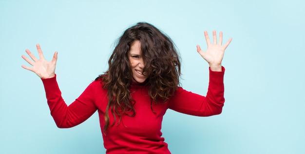 パニックや怒り、ショック、恐怖、激怒で叫んでいる若いきれいな女性、青い壁の上の頭の横にある手で