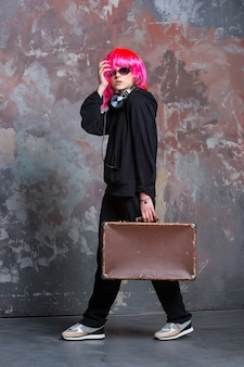 Young pretty woman or sexy girl with hair wig pink color in glasses and music headset, wears black cloth, holds brown suitcase on grey wall background, copy space