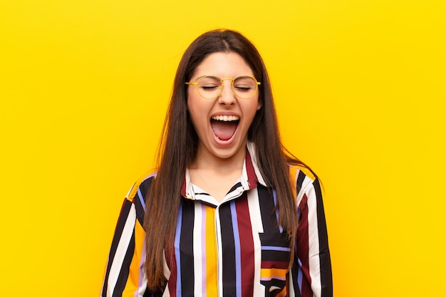 Young pretty woman shouting against yellow wall