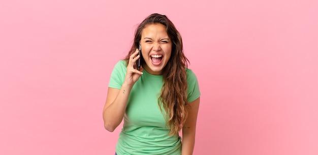 積極的に叫び、非常に怒っているように見え、スマートフォンを持っている若いきれいな女性