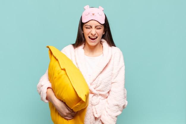 若いきれいな女性が積極的に叫び、非常に怒っている、イライラしている、憤慨している、またはイライラしているように見え、ノーと叫んでいます。パジャマのコンセプトを身に着けて目を覚ます