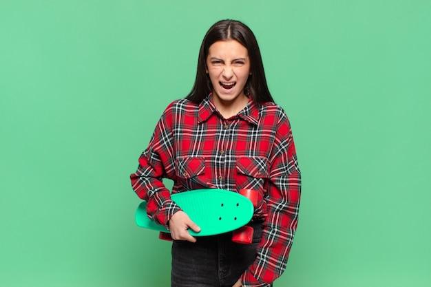 Молодая симпатичная женщина агрессивно кричит, выглядит очень сердитой, расстроенной, возмущенной или раздраженной, кричит «нет». скейтборд концепция