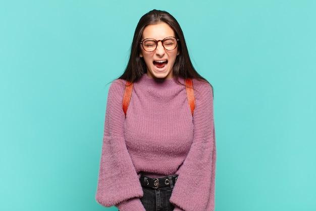 Молодая симпатичная женщина агрессивно кричит, выглядит очень сердитой, расстроенной, возмущенной или раздраженной, кричит «нет». студенческая концепция