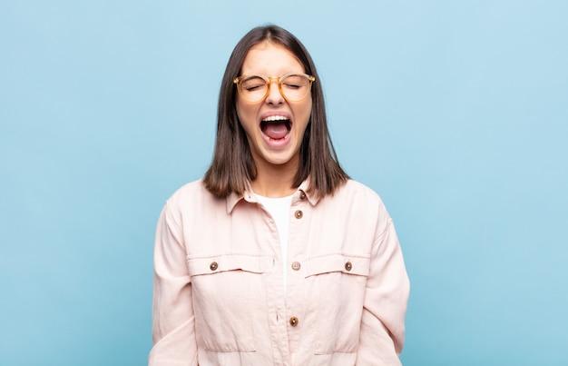 若いきれいな女性が積極的に叫び、非常に怒っている、欲求不満、憤慨している、またはイライラしているように見え、叫びません