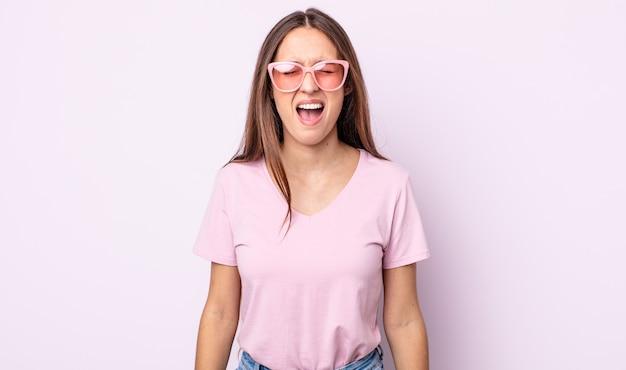 Молодая красивая женщина агрессивно кричит, выглядит очень сердитой. концепция розовых солнцезащитных очков