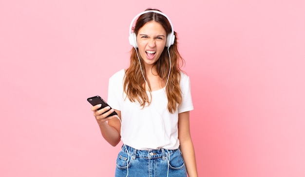 ヘッドフォンとスマートフォンで非常に怒っているように見える、積極的に叫んでいる若いきれいな女性