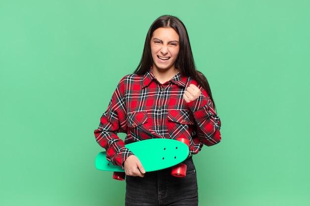 Молодая красивая женщина агрессивно кричит с сердитым выражением лица или со сжатыми кулаками, празднуя успех. скейтборд концепция