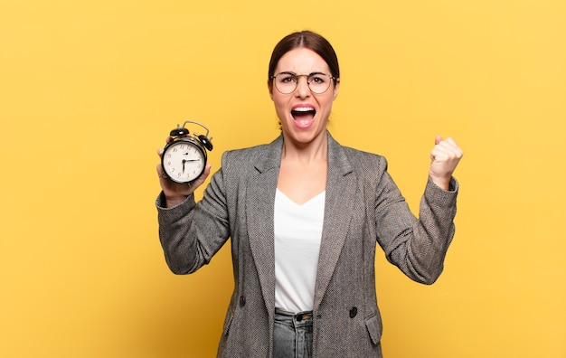 Young pretty woman shouting aggressively with an angry expression or with fists clenched celebrating success