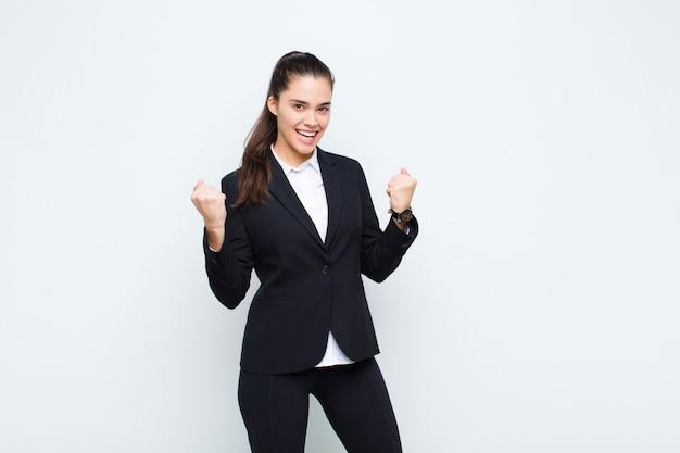 Молодая красивая женщина триумфально кричит, смеется и чувствует себя счастливой и взволнованной, празднуя успех бизнес-концепции