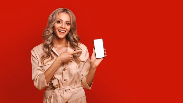 赤い背景の上に立っている間、携帯電話の白い画面に指を示す若いきれいな女性