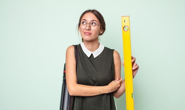 젊은 예쁜 여자 어깨를 으쓱하고 혼란스럽고 불확실한 느낌. 건축 개념