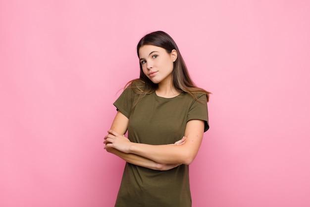 若いきれいな女性が肩をすくめて、混乱して不確実に感じて、腕を組んで困惑し、ピンクの壁に困惑した表情