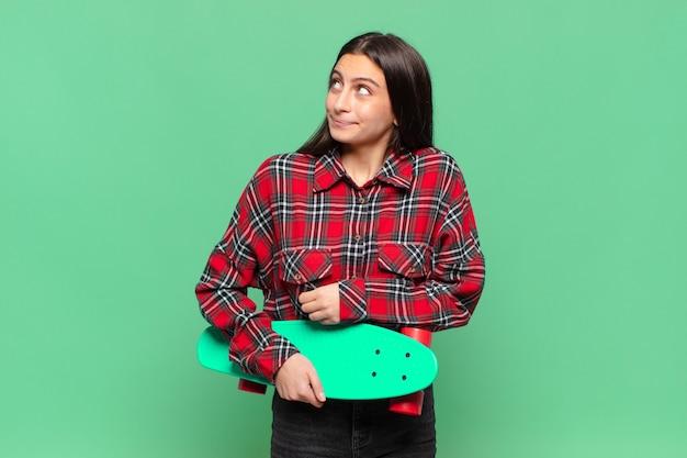 젊은 예쁜 여자 어깨를 으쓱하고, 혼란스럽고 불확실한 느낌, 팔로 의심하고 의아해 보이는 모습. 스케이트 보드 개념