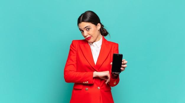 Молодая симпатичная женщина пожала плечами, чувствуя смущение и неуверенность, сомневаясь, скрестив руки и озадаченный взгляд. концепция смартфона